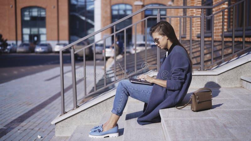 太阳镜的一个女孩在台阶工作户外 免版税库存图片
