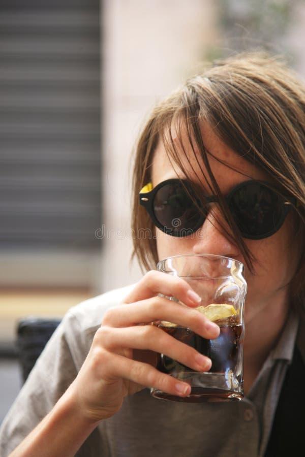 太阳镜的一个少年喝软饮料开会 库存图片