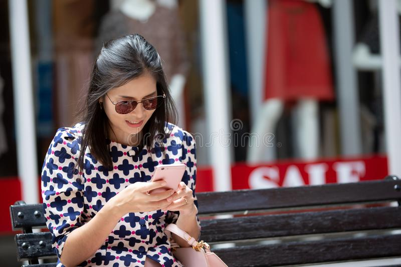 太阳镜的亚裔妇女使用一智能手机在购物中心 免版税图库摄影