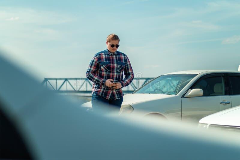 太阳镜的人在汽车附近使用电话 免版税图库摄影