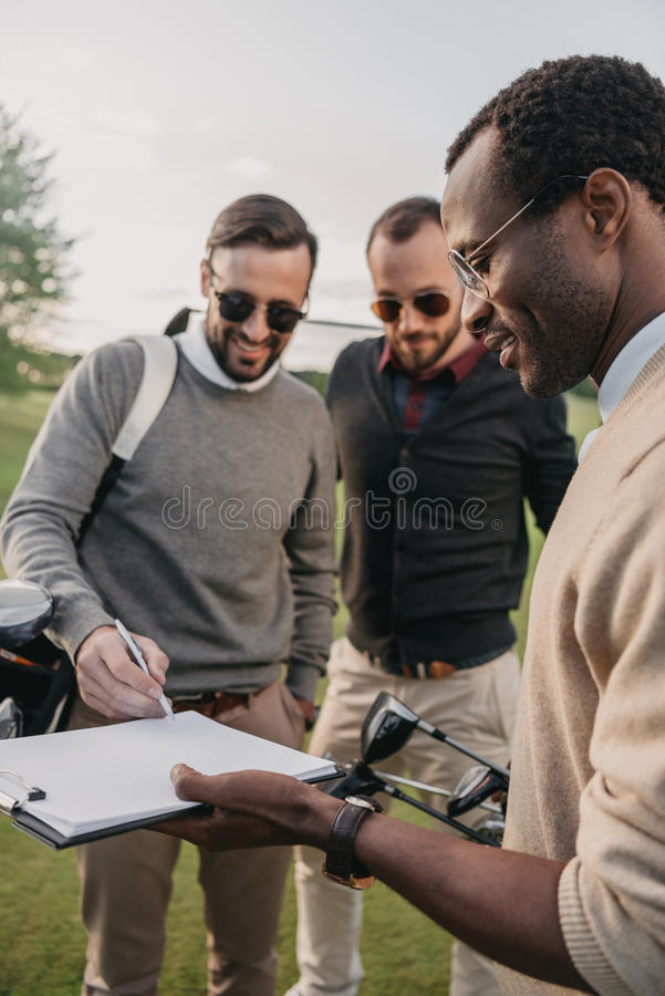 太阳镜的人签署在高尔夫球场的文件 库存照片
