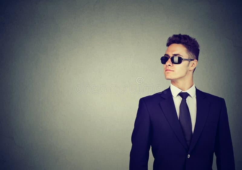 太阳镜的企业在灰色墙壁背景的人和衣服 免版税库存照片