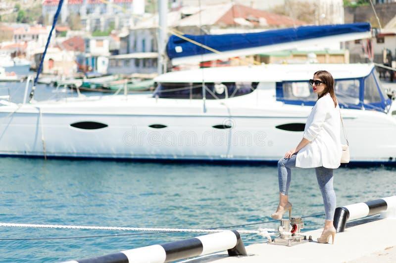 太阳镜的俏丽的妇女在豪华游艇附近的码头 太阳镜的愉快的女孩 r 免版税库存照片