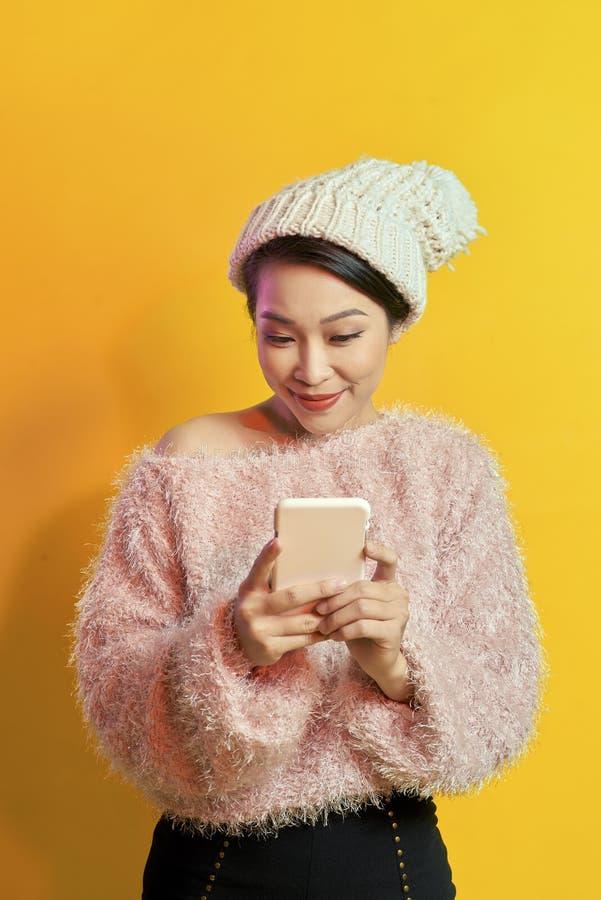 太阳镜的典雅的年轻女人和穿看手机屏幕的软的毛皮大衣 免版税库存图片