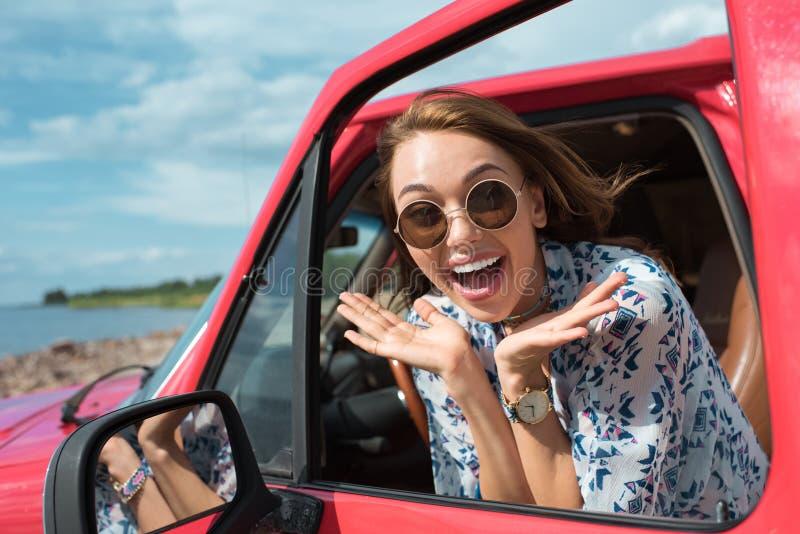 太阳镜的可爱的激动的女孩打手势和坐在汽车的 库存照片