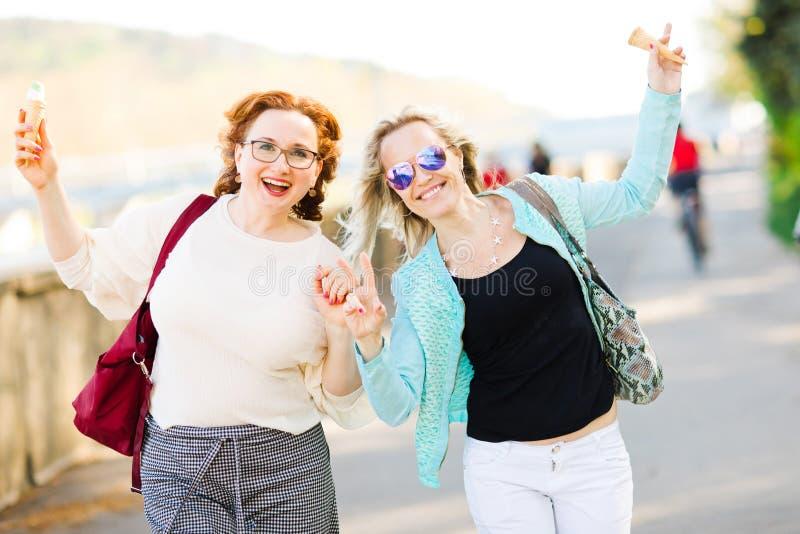 太阳镜的可爱的白肤金发的妇女走街市和吃冰淇淋-无忧无虑的妇女的 免版税库存图片