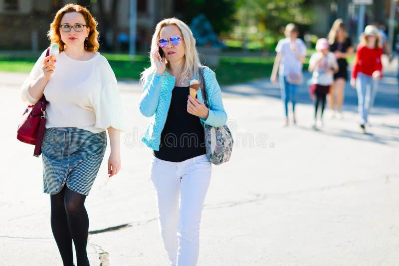 太阳镜的可爱的白肤金发的妇女走街市和eatin的 免版税图库摄影