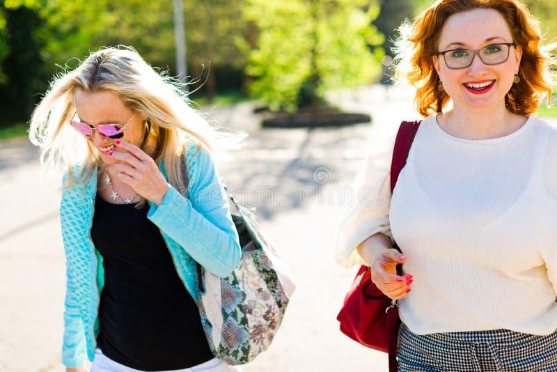 太阳镜的可爱的白肤金发的妇女走街市和eatin的 库存图片