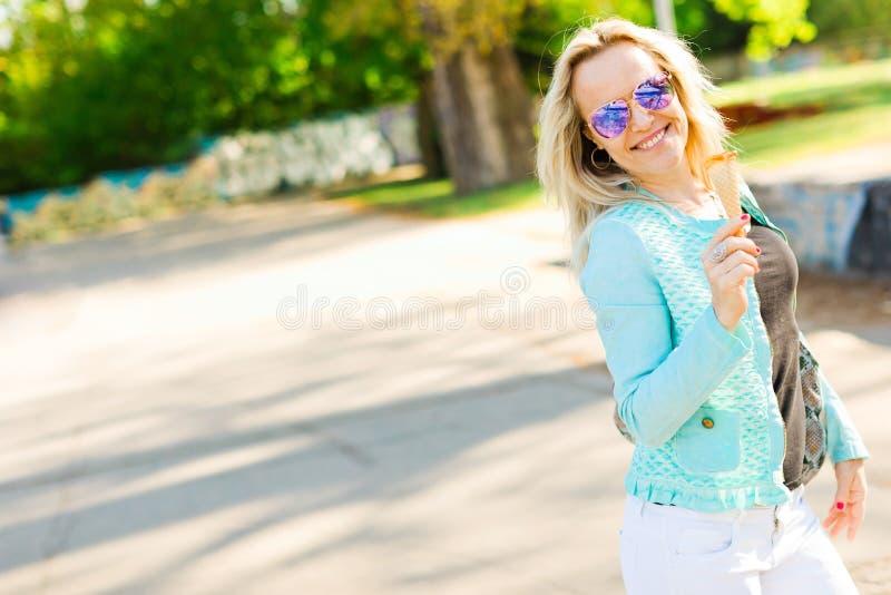 太阳镜的可爱的白肤金发的妇女-吃冰淇淋 库存图片