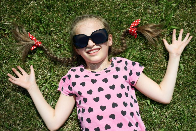 太阳镜的女孩在绿草说谎,穿戴在有心脏的桃红色衣裳,明亮的太阳,室外的夏天,顶视图 免版税库存图片