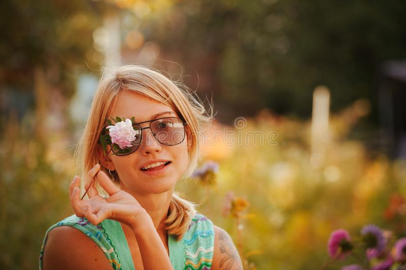太阳镜的女孩拿着在她的面孔前面的一朵花,闭上一只眼睛 俄国秀丽的概念,一个柔和的金发碧眼的女人与 免版税库存图片