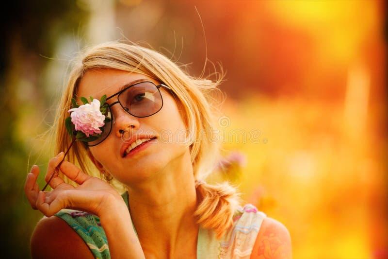 太阳镜的女孩拿着在她的面孔前面的一朵花,闭上一只眼睛 俄国秀丽的概念,一个柔和的金发碧眼的女人与 库存图片