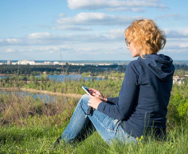 太阳镜的女孩有手机和汽车钥匙的看看法 库存照片