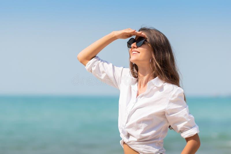 太阳镜的妇女微笑着在天空蔚蓝 库存照片