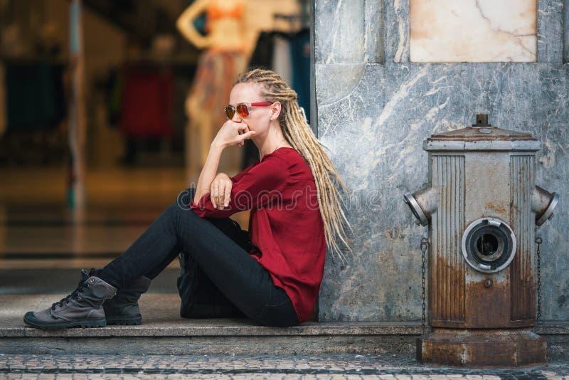 太阳镜的少妇有白肤金发的dreadlocks的周道地坐街道 库存图片