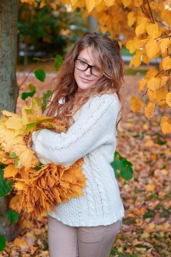 太阳镜的少妇走在秋天公园的 免版税库存照片