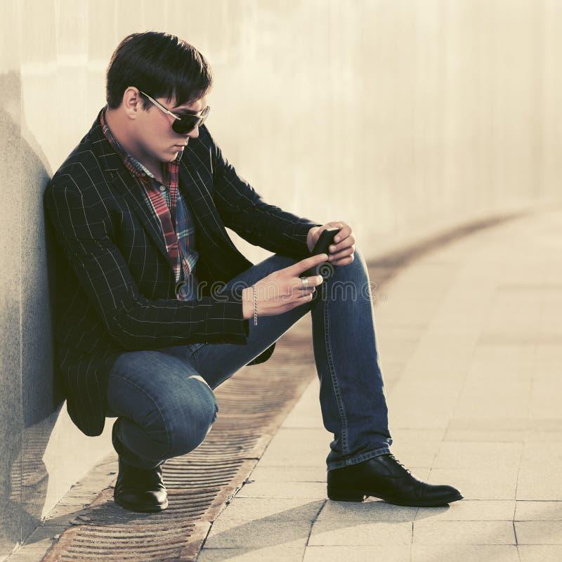 太阳镜的年轻商人使用在城市街道上的智能手机 库存照片