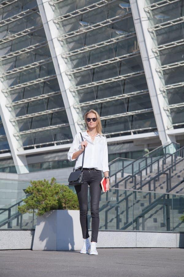 太阳镜的年轻女商人有在城市身分的袋子的与笔记本 免版税库存图片