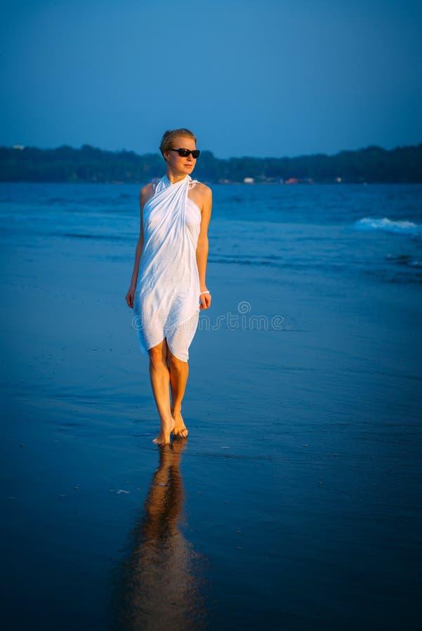 太阳镜的年轻白肤金发的妇女沿在海的海浪赤足走在一个温暖的夏天晚上 在日落的柔光,蓝色海 库存照片