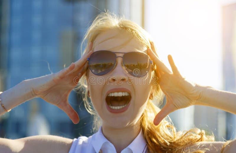 太阳镜的年轻金发碧眼的女人尖叫开放标尺并且拿着她的头、明亮的阳光和被弄脏的大厦在背景中 库存照片