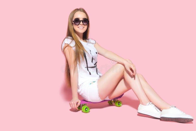 太阳镜的微笑的妇女在滑板 库存照片