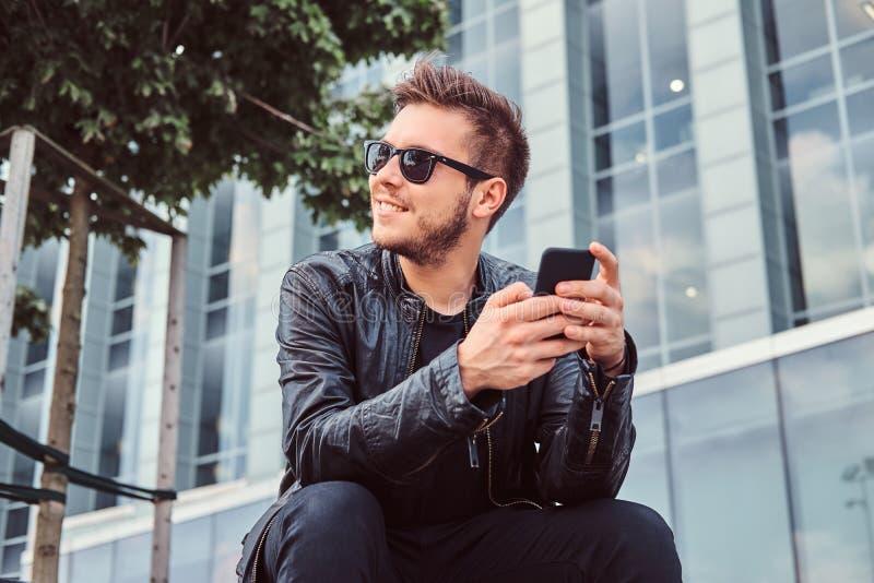 太阳镜的微笑的年轻人有在黑皮夹克穿戴的时髦的头发的拿着智能手机,当坐在a附近时 库存图片