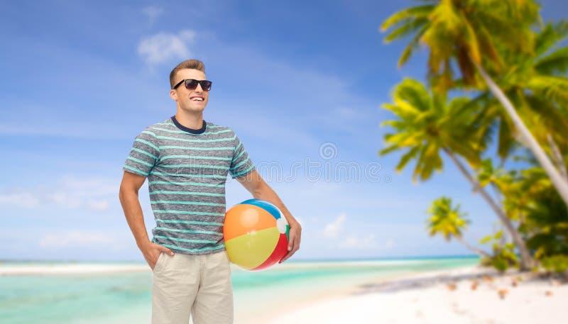 太阳镜的微笑的年轻人有海滩球的 免版税库存图片