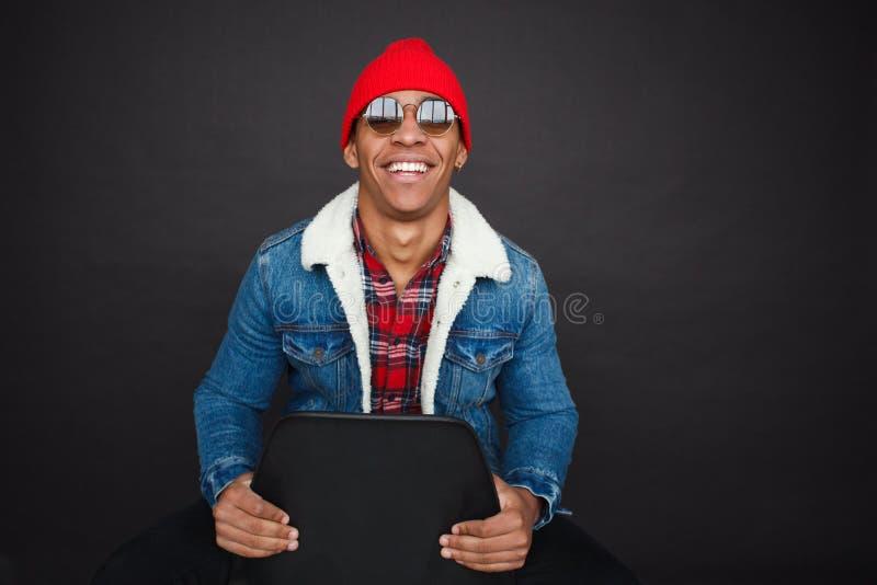 太阳镜的微笑的黑人在椅子 免版税图库摄影