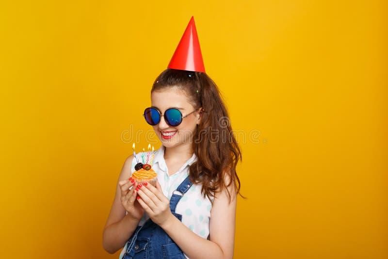 太阳镜的愉快的女孩,在黄色背景,拿着在手上与蜡烛的一块杯形蛋糕 库存图片