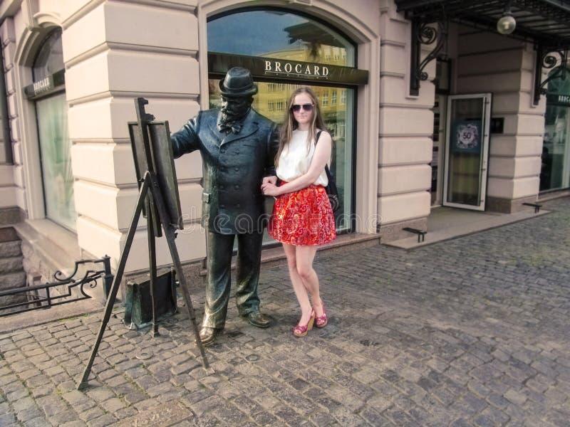 太阳镜的旅游女孩在画家附近站立Ignac Roskovics的雕象在乌日戈罗德 免版税库存照片