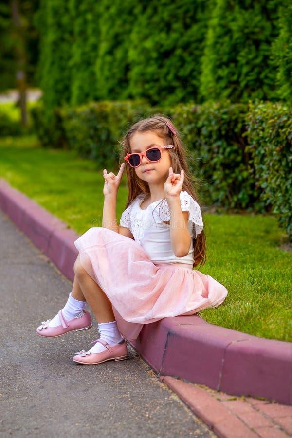 太阳镜的时兴的小女孩在街道上 垂直的酸碱度 图库摄影