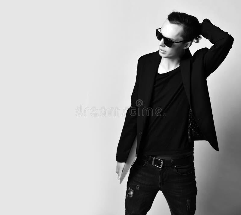 太阳镜的时髦的人,T恤杉,夹克,有膝上型计算机的破旧的牛仔裤在他的手上固定他创造性的理发和神色在文本空间 库存图片