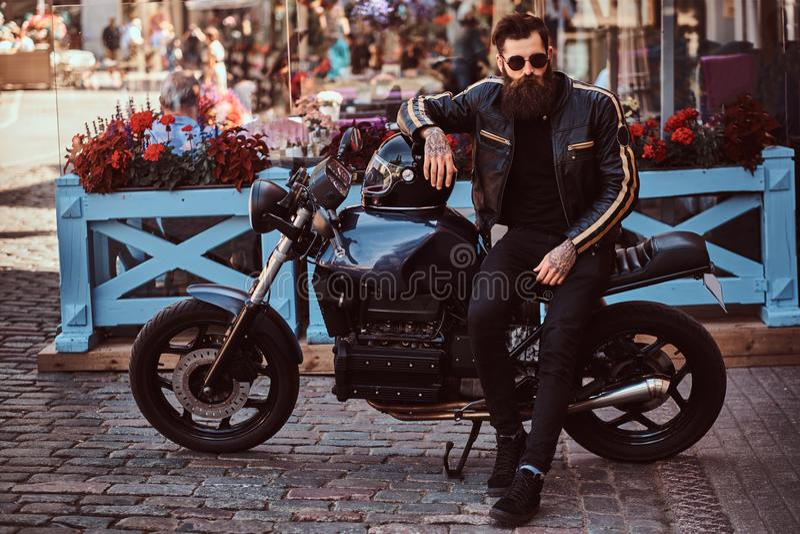 太阳镜的时髦的时兴的骑自行车的人在黑皮夹克穿戴了,坐他定制的减速火箭的摩托车 免版税库存图片
