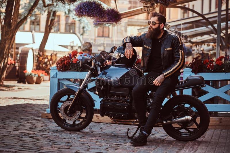太阳镜的时髦的时兴的骑自行车的人在黑皮夹克穿戴了,坐他定制的减速火箭的摩托车 免版税库存照片