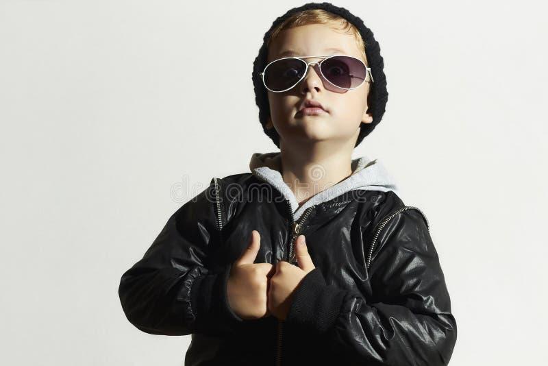 太阳镜的时兴的滑稽的孩子 黑色盖帽 冬天样式 摆在小男孩 儿童时尚 孩子 免版税图库摄影