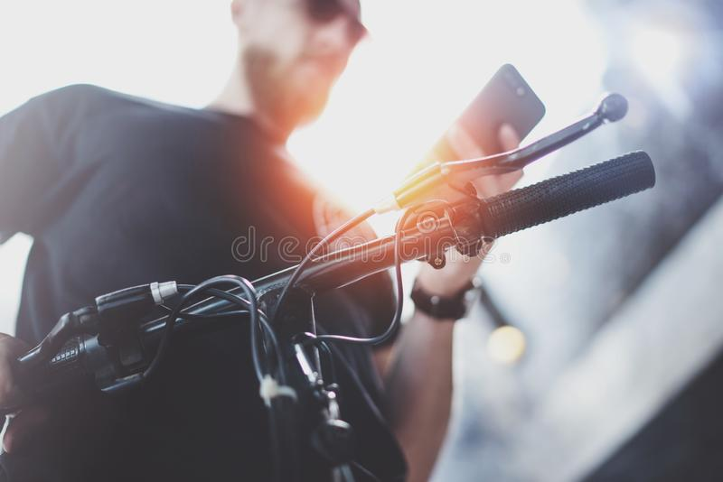 太阳镜的有胡子的肌肉被刺字的行家使用在乘坐的智能手机乘电滑行车以后在城市 免版税图库摄影