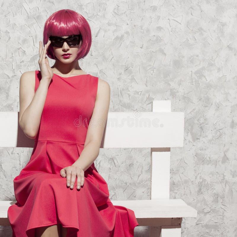 太阳镜的流行艺术妇女坐白色长凳 库存图片