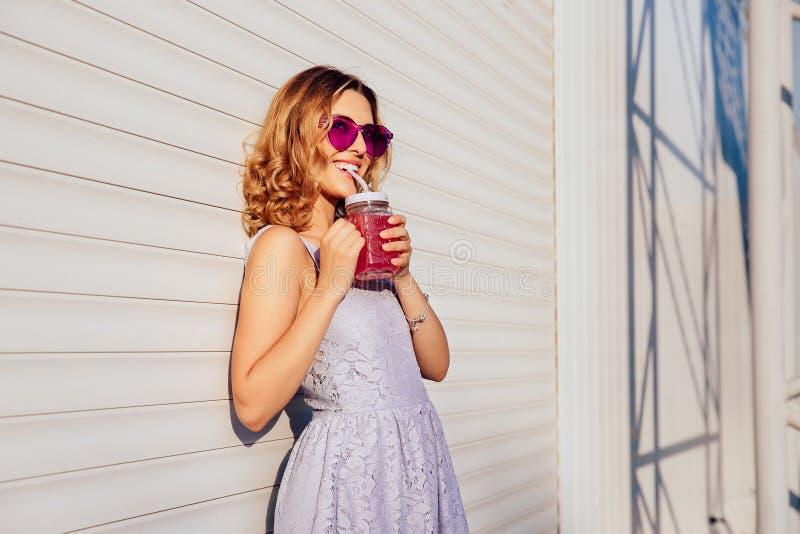 太阳镜的滑稽的女孩喝冷的果子饮料的,在好日子 免版税图库摄影