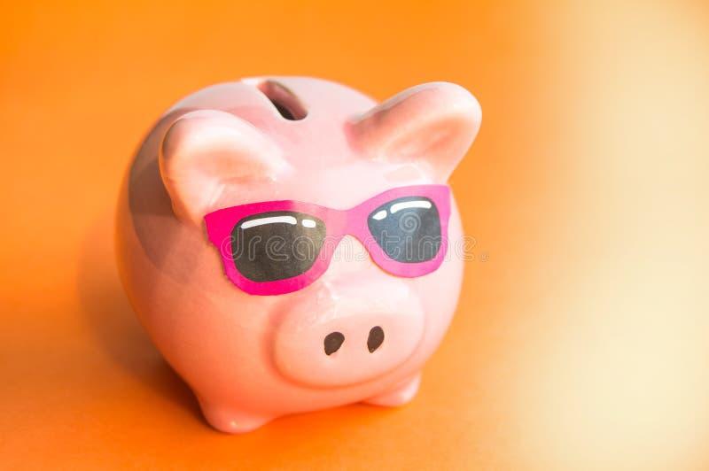 太阳镜的滑稽的存钱罐在橙色背景,阳光,拷贝空间,节约金钱概念为暑假 免版税库存照片