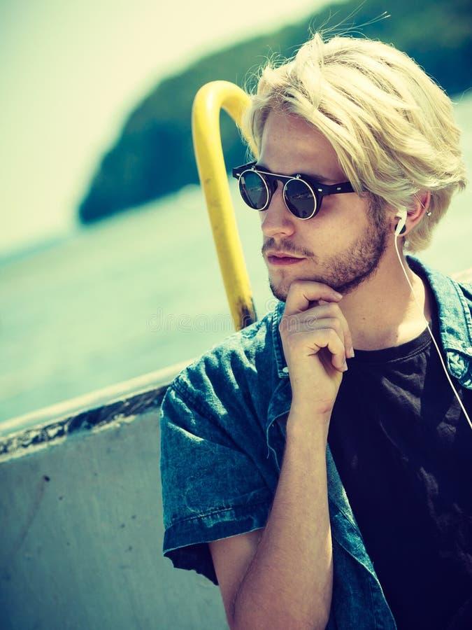 太阳镜的白肤金发的人听到音乐的 免版税库存照片