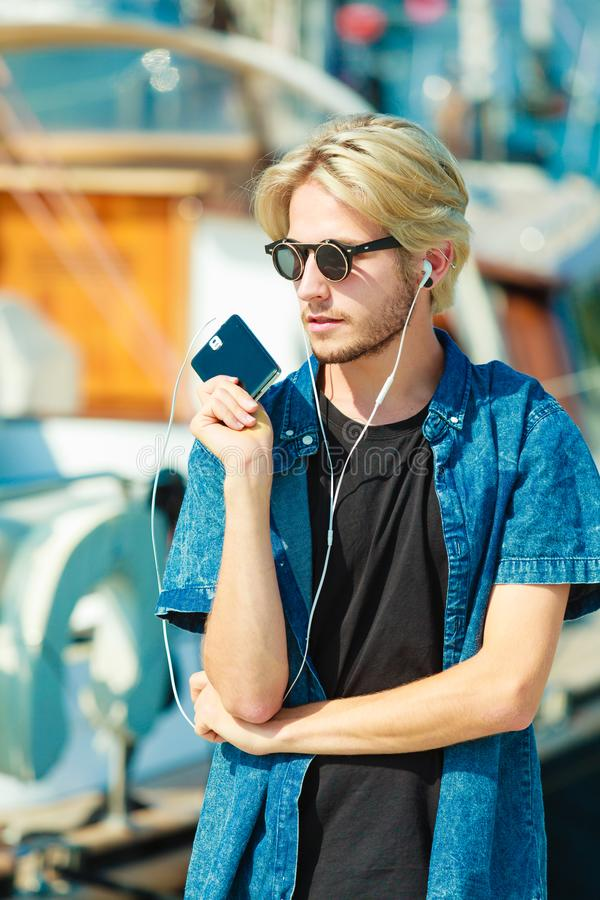 太阳镜的白肤金发的人听到音乐的 图库摄影