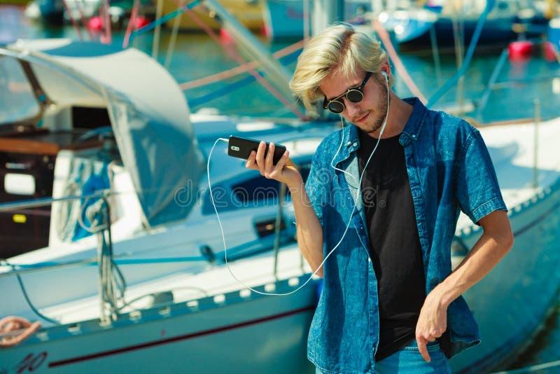 太阳镜的白肤金发的人听到音乐的 免版税图库摄影