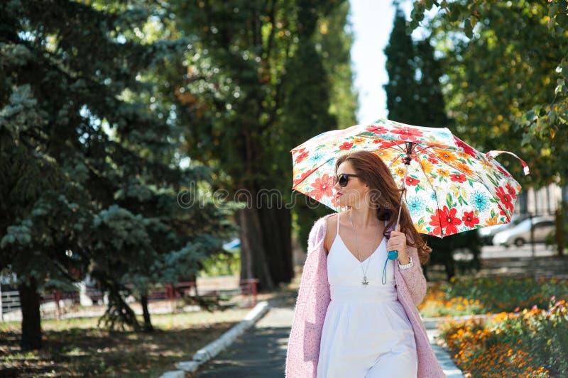 太阳镜的美丽的妇女有伞的走在公园的 图库摄影