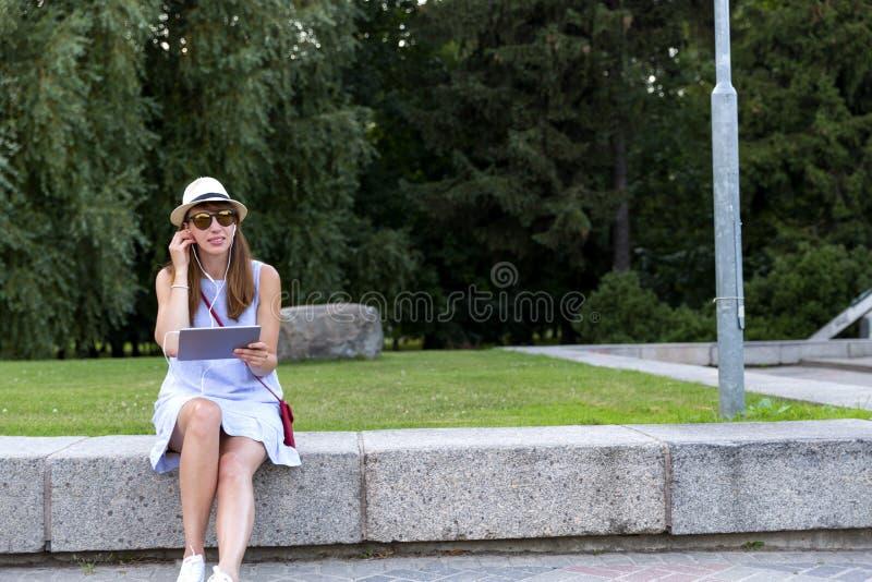 太阳镜的美丽的少妇听到在坐的耳机的音乐的观点的户外 图库摄影