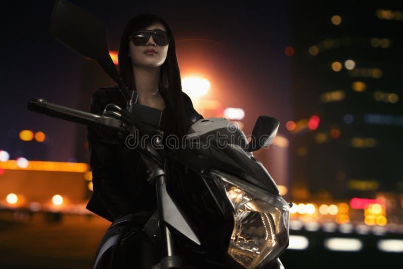 太阳镜的美丽的少妇坐摩托车在夜间在北京 免版税库存照片