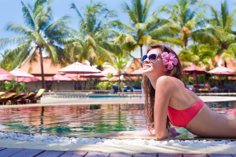 太阳镜的美丽的少妇有在豪华水池的异乎寻常的鸡尾酒的 库存图片