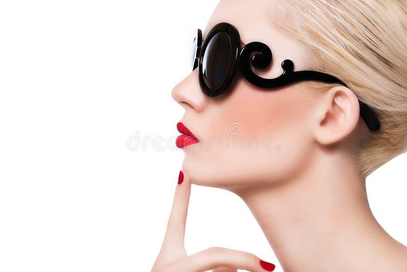 太阳镜的美丽的白肤金发的女孩有在白色backg的红色嘴唇的 免版税库存图片