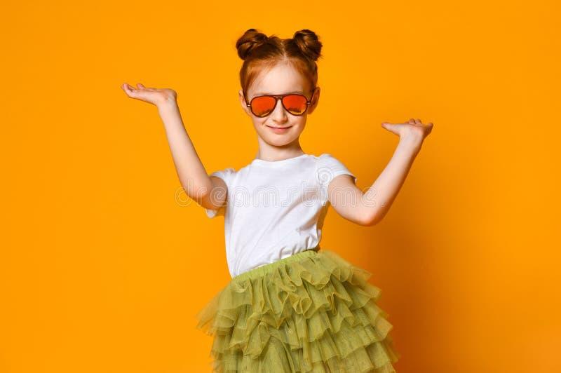 太阳镜的美丽的红发女孩高兴涂她的胳膊对边 免版税图库摄影