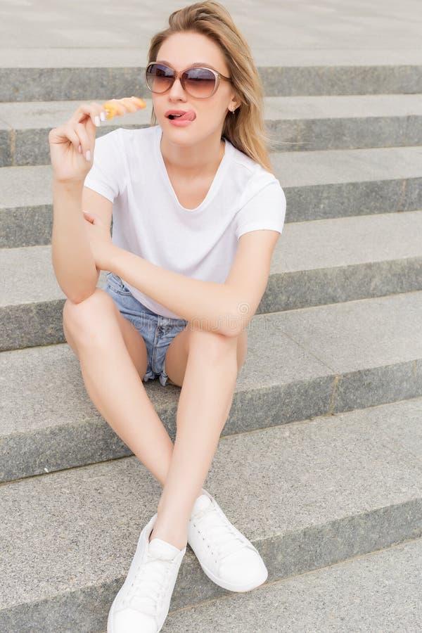 太阳镜的美丽的年轻性感的女孩吃在梯子的冰淇凌和舔肥满嘴唇的每明亮的晴朗的热的天 免版税库存照片