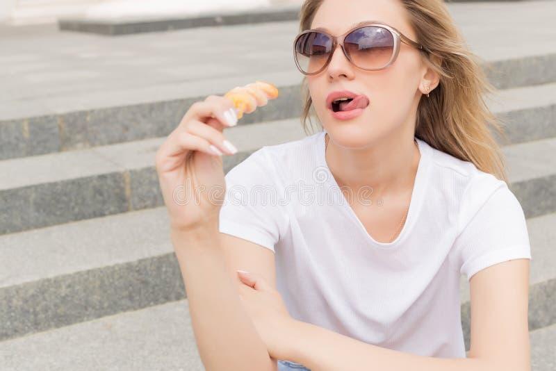 太阳镜的美丽的年轻性感的女孩吃在梯子的冰淇凌和舔肥满嘴唇的每明亮的晴朗的热的天 免版税库存图片